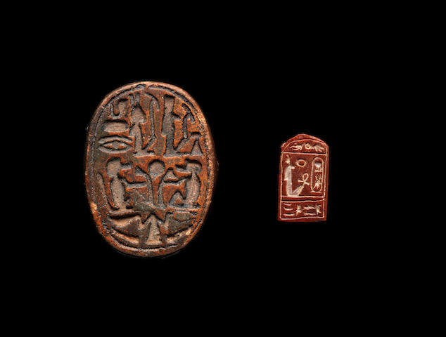 An Egyptian red jasper cartouche plaque and a large Egyptian clay scarab, 2
