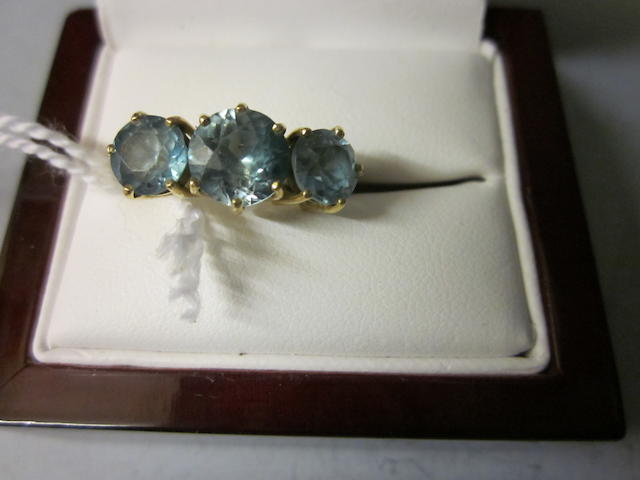 An 18ct gold three stone blue zircon ring,