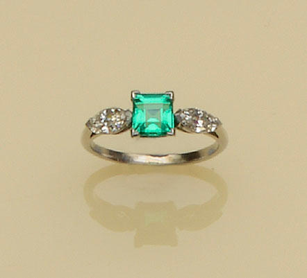 An emerald and diamond three stone ring