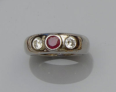 An 18ct white gold ruby and diamond three stone ring