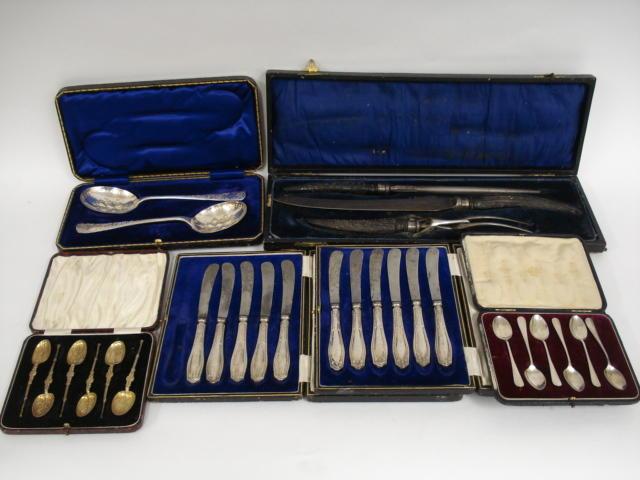 A selection of spoon sets and other flatwares comprising a carving set; two carved spoon sets (six in each); two knife sets (six and five); carved pair of serving spoons (plated) and a bag of twenty four various pieces (large quantity)