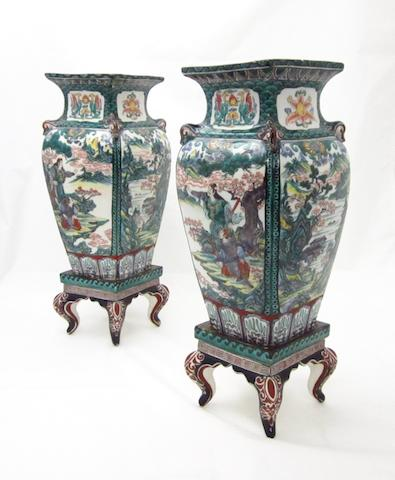 A mirrored pair of Ao-Kutani style vases on stands Meiji