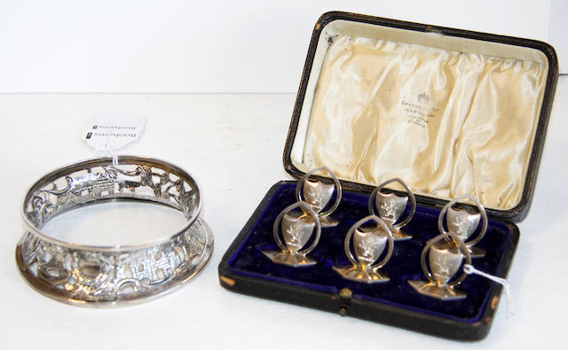A set of six George V menu holders,each with a crest-engraved shield, Birmingha, 1912 (cased) and an irish miniature dish ring, in 18th Century style, pierce-decorated with buildings, figures and animals, Dublin 1919, 11cm diameter (7).