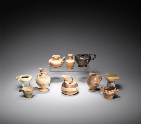 Nine Corinthian miniature terracotta vessels and a South Italian black glazed feeder, 10