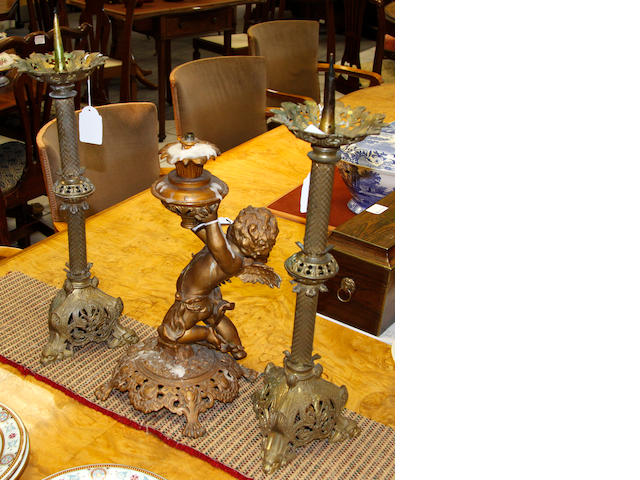 A spelter putto lamp and a pair of 'Gothic' candlesticks