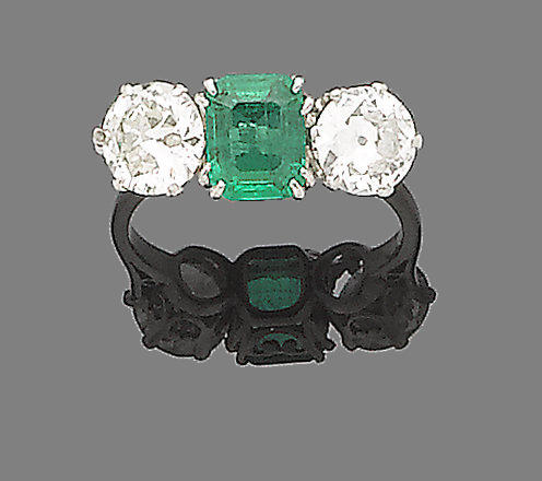 An emerald and diamond three-stone ring