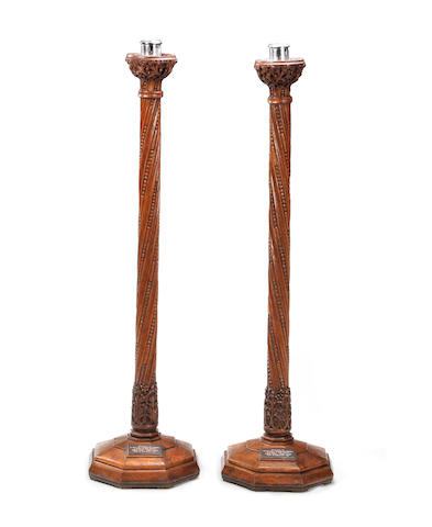 A pair of carved oak torcheres Each bearing a plaque reading 'Presented by / The Revd. and Mrs H. Lenehan (nee Simpson) / in memory of their parents / Thomas & Mary - James & Alice / Feast of Dedication - 1939'