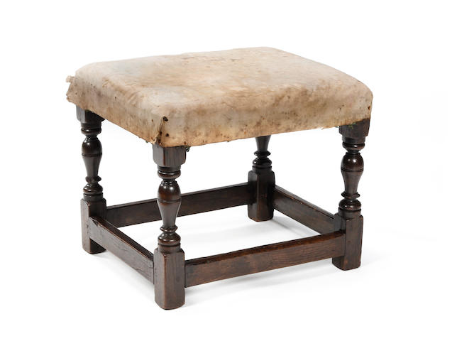 An early 18th century style oak and upholsered stool