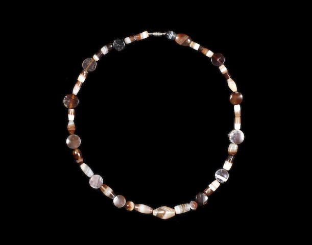 A Western Asiatic dark banded agate necklace