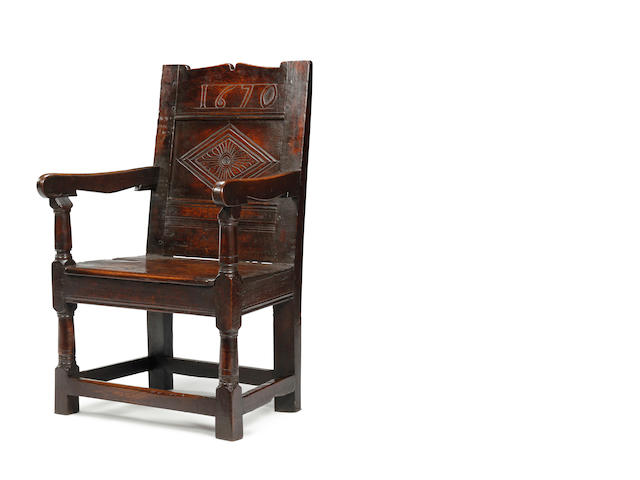 A Charles II oak panel back open armchair, dated