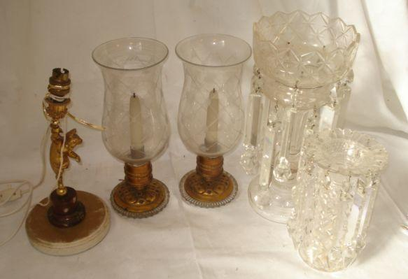 A pair of gilt metal lamps, on pierced domed and cut glass bases, fitted with gilt metal mounted lattice cut glass storm shades, 31cm, a cut glass lustre hung with triangular section and facet cut glass drops, 36cm, a damaged and incomplete cut glass lustre hanging from a cut glass vase, and a gilt metal cherub candlestick on rouge Royale marble socle adapted for electricity. (5)