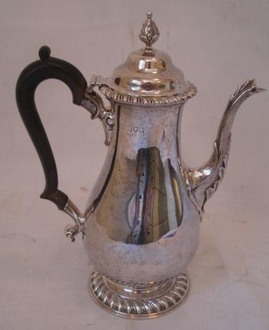 An earl 20th Century silver coffee pot, in the George II style, the pear shaped body on gadrooned circular foot domed cover and leaf capped spout, blackwood handle, by 1914, 25.5cm, 20oz gross.