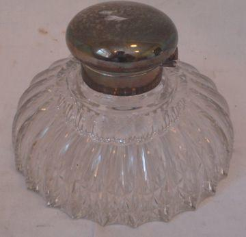 An Edwardian silver mounted cut glass inkwell, the plain hinged cover to reveal a glass liner, 15cm diameter, silver hallmarked Sheffield 1910.