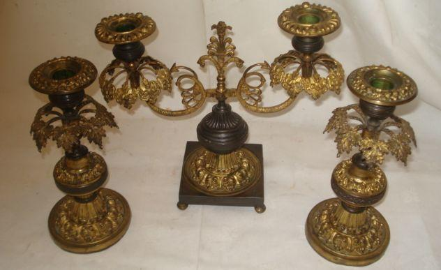 A gilt brass and bronze twin branch candlebra, circa 1820, the scaly serpent arms with anthemion bracket supporting leafy collar sconces and hung with glass drops, on square base and turned feet, 23cm, together with a pair of similar candlesticks. (3)