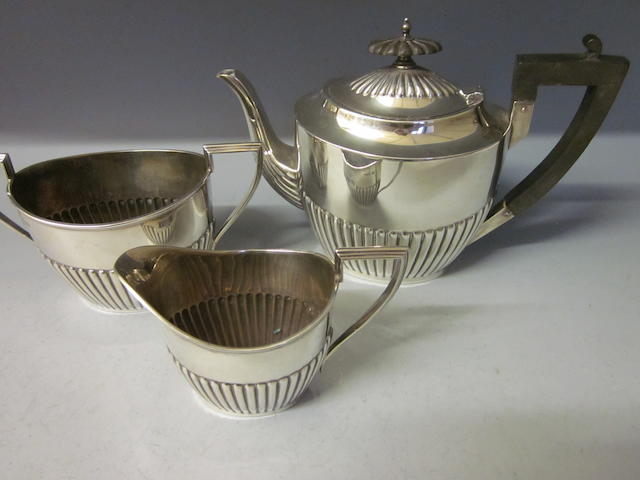 A three piece silver tea service,  by Walker and Hall,  Sheffield 1917,  (3)