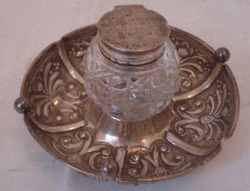 An Edwardian silver inkstand, the cut glass bottle with inscribed hinged cover on a circular scroll decorated base, 11cm diameter, 1905.