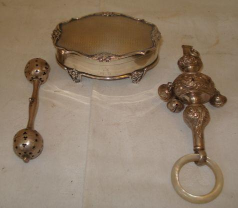 A pretty Edwardian silver jewellery box, of oval shape with flowerhead cast border, on four flower and tendril panel feet, by Goldsmiths & Silversmiths, 1907, 9 x 6cm, an embossed silver combined whistle and rattle with mother of pearl feather, Birmingham 1910 and another rattle of dumbell form, Birmingham 1900. (3)