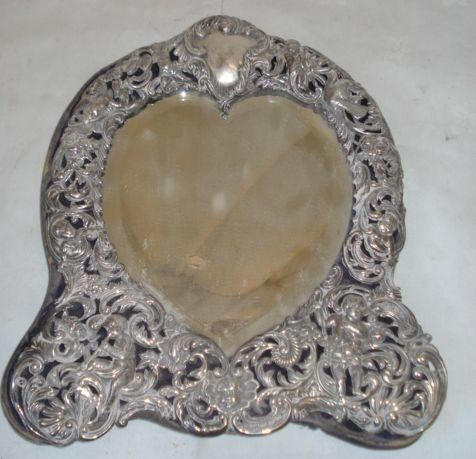 A Victorian silver faced easel dressing table mirror, the bevelled heart shaped plate within a pierced frame decorated scroll cherubs and birds, by William Comyns 1896, 27cm, front detached.