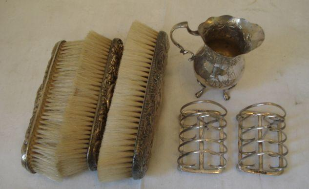 A pear shape cream jug, embossed ribbon tied swags on four cabriole legs, import marks for 1894, a pair of breakfast toast racks with heart shaped wire divisions, Sheffield 1907, and three silver backed clothes brushes.