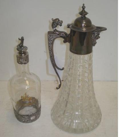 A modern silver mounted cut glass claret jug, Roberts & Belk, Sheffield 1979, in late Victorian style with hinged cover, and 'C' scroll handle surmounted by an animal mask, 32cm, and an ornate continental silver mounted glass liqueur decanter, late 19th Century, pierced and embossed with cherubs and lattice work, the stopper surmounted by putti, 24cm. (2)