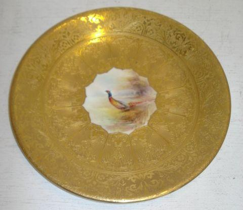A Royal Worcester porcelain cabinet plate, centrally painted with a pheasant in a landscape by Rose, shape no. 3307, within a wide finely gilt foliate border, 23.5cm.