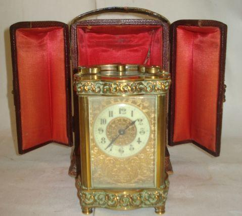 An early 20th Century brass cased carriage timepiece, circular dial with pierced and engraved mask, moulded brass serpentine shaped case, display box.