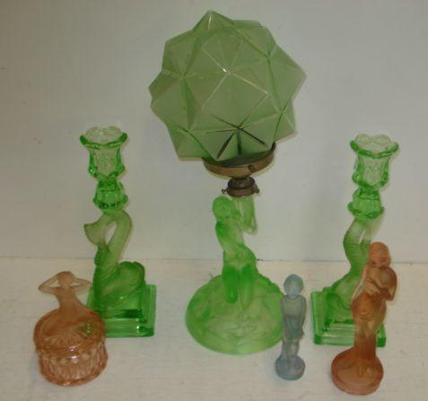 An Art Deco moulded green cloud glass table lamp, the semi nude female subject supporting the shade aloft, pair of similar style and colour dolphin candlesticks and a collection of other moulded coloured glasswares of the period including vases and centrepieces.