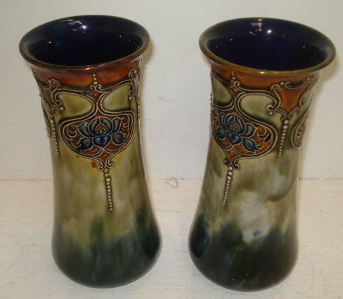 A pair of Royal Doulton baluster vases, tube lined with an upper frieze of repeated foliate design, impressed marks, 24cm.