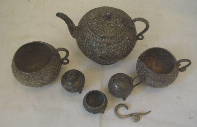 An Indian silver three piece silver tea set, each piece of globular form with serpent handles, teapot with hinged lid, sugar bowl and milk jug and decorated with scrolling foliates, together with a matching three piece cruet.
