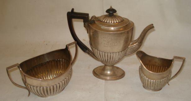A late Victorian silver coffee pot, of half gadrooned vase form, 1892, matching two handled sugar basin and milk jug 1894, 19ozs gross.