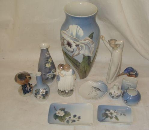 A large Royal Copenhagen flower vase, decorated with a lily on a blue ground, 33cm, a pear shaped vase decorated with flowers, 19cm, two Copenhagen bird figure groups, Lladro figure and seven other pieces. (12)