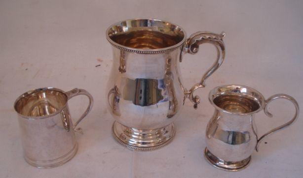 A Victorian baluster mug, with bead rim and leaf capped scroll handle, 13cm, 1890, a small baluster mug with high loop handle, 1919, and a small tapering cylindrical mug with banded foot, Sheffield 1979, 20ozs total. (3)