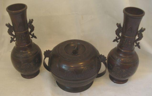 A 20th Century Chinese patinated bronze, circular two handled box and flush cover, decorated lappett panels, 22cm diameter, together with a pair of patinated bronze vases, 31cm. (4)