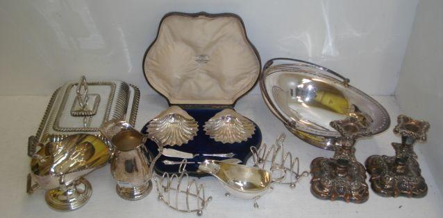 A cased pair of George V silver scallop shell butter dishes, Goldsmiths & Silversmiths Company, 1912, and a pair of butter knives, and the following silver, a pair of late Victorian wire work navette shape toast racks, Birmingham 1898, and a George III style gadroon edge sauce boat, Birmingham 1970, 13ozs, and the following electroplate a George III style navette shape cake basket, by Elkington, George III style entree dish, pair of George IV style candlesticks, sugar scuttle and scoop and cream jug.