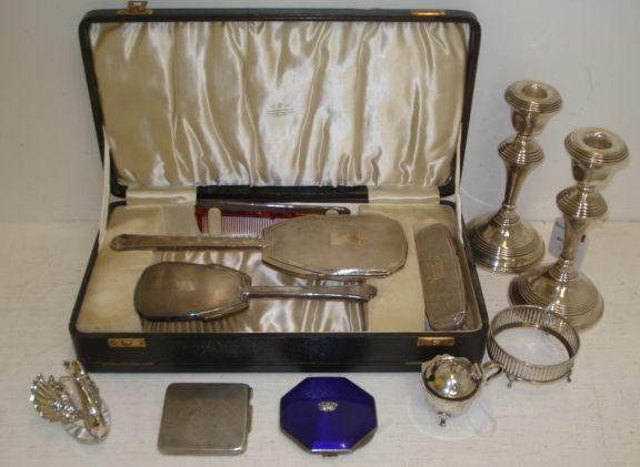 A cased Art Deco engine turned silver mounted four piece dressing table set, and the following silver, a mounted glass swan salt cellar and spoon, English Import marks, pair of George III style candlesticks, with turned stems, mustard pot in Georgian style, sweetmeat dish frame, with slat pierced sides, lacks glass liner, octagonal blue guilloche enamelled compact applied with a naval crown and a foreign metalware engine turned compact, stamped '800'.