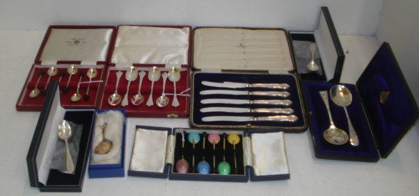 A set of six Art Deco style silver gilt coffee spoons, Birmingham 1962, the reverse of the bowl guilloche enamelled in differing colours and the following cased silver flatware, set of six 'bean end' coffee spoons, set of six trefid end teaspoons set of five tea knives with electroplate blades, trefid end caddy spoon, pair of teaspoons with millennium marked, also a pair of electroplate preserve spoons.