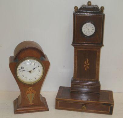 A late Victorian silver cased open face pocket watch, in a George III style mahogany crossbanded boxwood and ebony strung table top case in the form of a longcse clock, with a projecting drawer below, 38cm, and an Art Nouveau walnut and decorated mantel timepiece in shaped case. (2)
