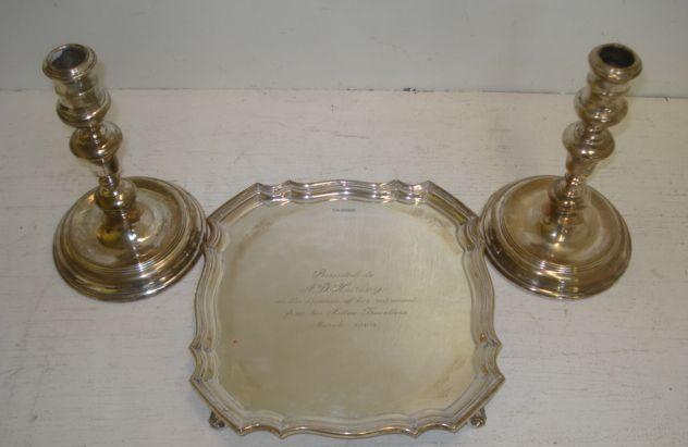 A George III style shaped square salver, Walker & Hall, Sheffield 1959, 14ozs, 21cm, Presentation Inscription, and a pair of early 18th Century style silver candlesticks, 1969, with knop stems and sunken circular bases, 18.5cm. (3)