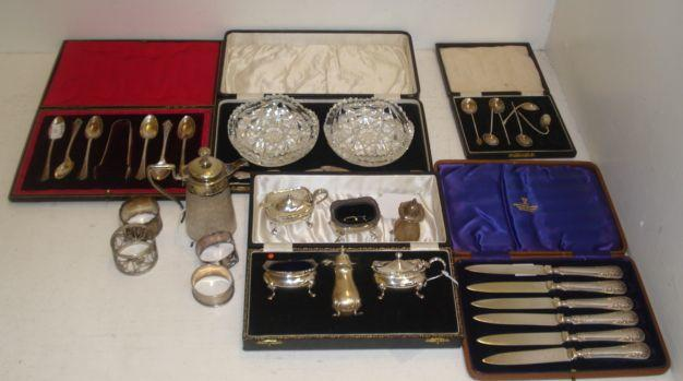 Two Georgian style silver three piece condiment sets, Birmingham 1955 and 1964, one cased, and the following silver, three various napkin rings, cased pair of cut glass butter dishes, with silver knives, cased set of six fruit knives with electroplate blades, cased set of six demi tasse, damaged, also a cased set of electroplate teaspoons, a napkin ring and later Victorian mounted miniature cut glass claret jug.