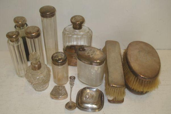 A part set of Edwardian/George V silver mounted dressing case fittings, various dates and markers, comprising a mounted glass spirits flask with detachable cup, six mounted glass bottles and jars, pairs of mounted military hair and clothes brushes, monogrammed and the following silver, a mounted glass perfume bottle, also the following metalwares a pricket candlestick, on shaped square base, foliate engraved pill box and a fancy spoon, all stamped '800'.