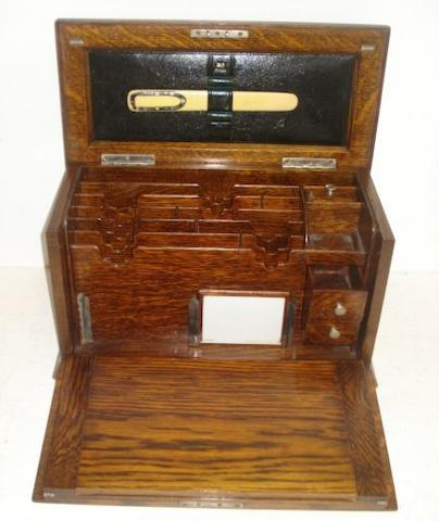 An Edwardian oak desk top stationery and writing cabinet, the hinged top and fall front enclosing a fitted interior, 39cm, and a leather suitcase, the moire silk lined interior fitted with a tortoiseshell dressing table set, foul weather cover.