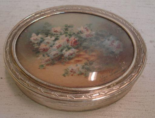 A continental oval engine turned silver box, Mappin & Webb, import marks for 1911, the pull-off cover inset with a glazed watercolour still life study of flowers, signed, and enclosing a gilt lined interior, 9.5cm, 6ozs gross.
