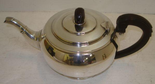 An Art Deco circular silver teapot, W Neale & Sons, Birmingham 1938, with composition handle and finial to the hinged cover, 20ozs.