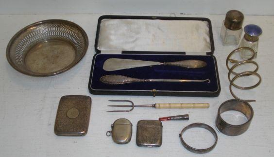 A George V circular silver bon bon dish, Chester 1922, with pierced sides, and the following silver, a late Victorian leafy scroll engraved cigarette case, Birmingham 1900, two vesta cases, two mounted glass salts jars, one guilloche enamelled, two hinged engraved bangles, cased mounted shoe horn and button hook, ham fork with faux bamboo handle, mounted cigarette holder, also an electroplate bracelet, 11ozs weighable.