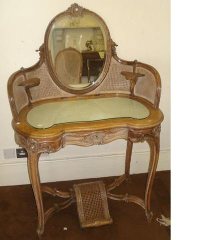 A French late 19th Century foliate carved walnut dressing table, in Louis XV style, the carved double caned inset back with a central oval mirror, the inset top of shaped outline above a frieze drawer, on slender cabriole legs united by an 'X' stretcher, with caned foot rest, 92cm.