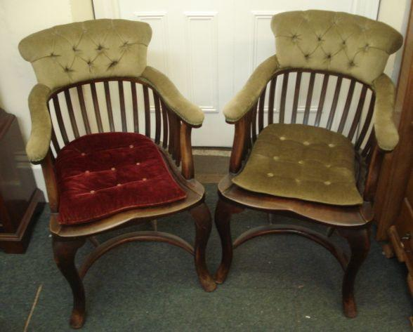 A pair of Edwardian mahogany Windsor elbow chairs, with comb backs, button down upholstered, on cabriole legs united by crinoline stretchers.