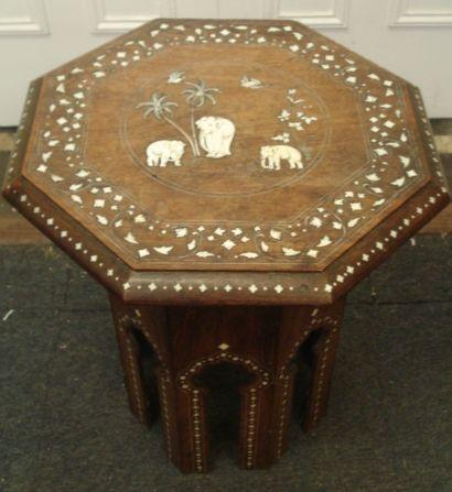 An early 20th Century Indian octagonal hardwood ivory inlaid low table, with hinged folding sides, the top centred by a panel of elephants, 49cm.