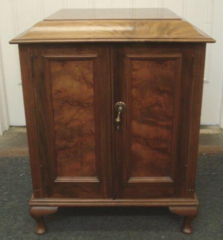 An Edwardian walnut cabinet, fitted with six drawers, enclosed by a pair of doors, containing a large quantity of flatware and cutlery including a set of dessert eaters and a set of fish eaters, the cabinet, 50cm.