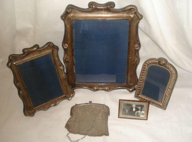 A large 20th Century silver faced easel photograph frame, with scrolled border, size 25 x 20cm, another 17.5 x 12cm, an arched top frame, a faux tortoiseshell frame and mesh bag. (5)