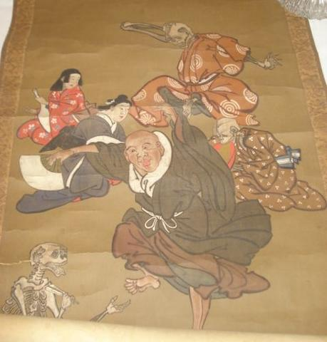 A late 19th Century Japanese scroll painting, depicting figures rakan and skeletons bone ended scroll caps.